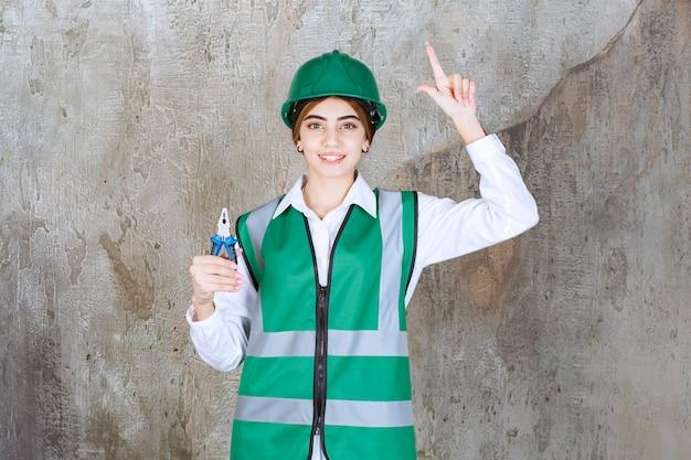 ピラールとポーズをとって緑の制服を着た若い女性請負業者