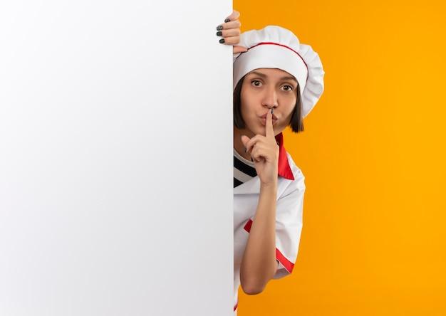 Giovane cuoco femminile in uniforme del cuoco unico che gesturing silenzio e che guarda l'obbiettivo da dietro il muro bianco isolato su priorità bassa arancione con lo spazio della copia
