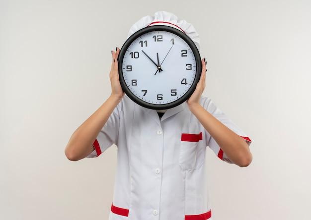 Giovane cuoco femminile in uniforme del cuoco unico che tiene e che si nasconde dietro l'orologio isolato su fondo bianco