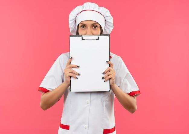 Giovane cuoco femminile in uniforme del cuoco unico che tiene e che guarda l'obbiettivo da dietro la lavagna per appunti isolata su fondo rosa con lo spazio della copia