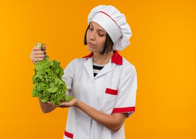 Giovane cuoco femminile in uniforme del cuoco unico che tiene e che esamina lattuga isolata su fondo arancio con lo spazio della copia
