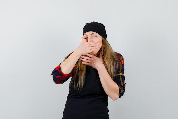 黒いエプロンの咳で若い女性の料理人