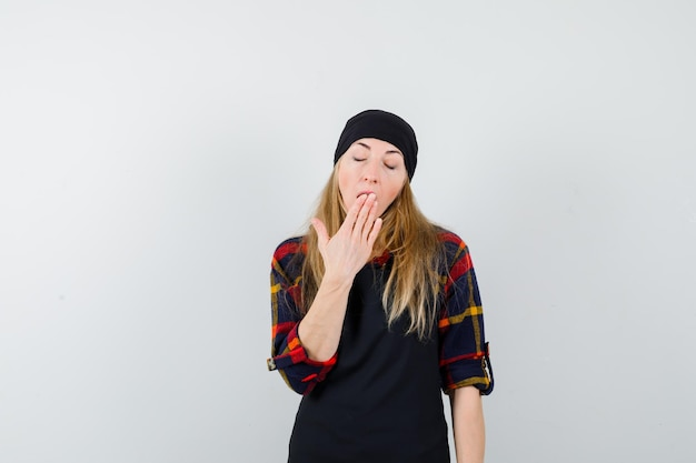 あくびをする黒いエプロンで若い女性の料理人