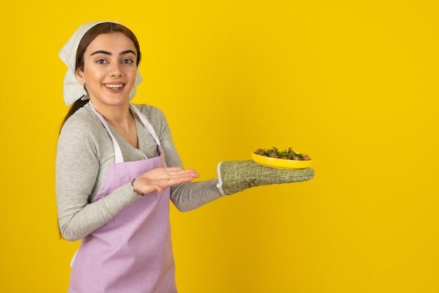 노란색 벽 위에 튀긴 버섯 접시를 들고 앞치마에 젊은 여성 요리사.