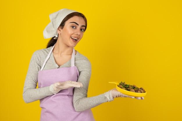 Молодая женщина-повар в фартуке, держа тарелку с жареными грибами над желтой стеной.
