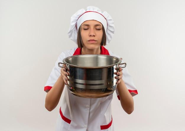 コピースペースと白い背景で隔離の目を閉じて鍋を保持し、スニッフィングシェフの制服を着た若い女性料理