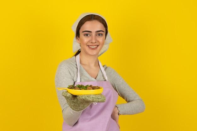 보라색 앞치마를 입은 젊은 여성 요리사가 노란색 벽에 튀긴 버섯 접시와 함께 포즈를 취합니다.