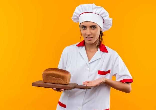 コピースペースと孤立した黄色の壁のまな板にパンを保持しているシェフの制服を着た若い女性料理人