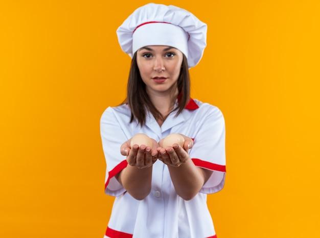 オレンジ色の壁に分離された卵を差し出すシェフの制服を着た若い女性料理人