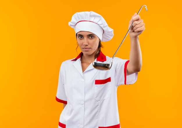 Молодая женщина-повар в униформе шеф-повара протягивает ковш на изолированной желтой стене с копией пространства