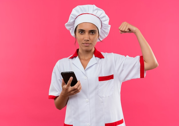 Young female cook wearing chef uniform holding phone and doing strong gesture on isolated pink wall with copy space