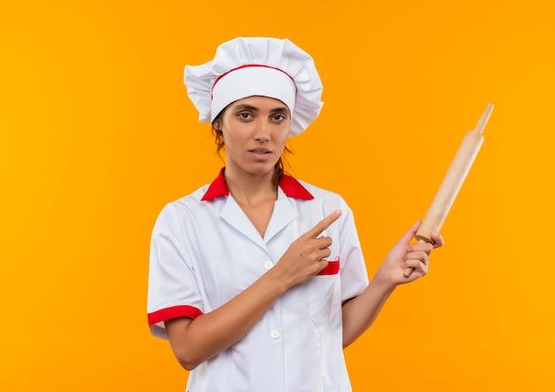 Giovane cuoco femminile che indossa la tenuta uniforme dello chef e indica il mattarello sulla parete gialla isolata con spazio di copia