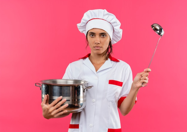 Young female cook wearing chef uniform holding saucepan and ladle on isolated pink wall with copy space