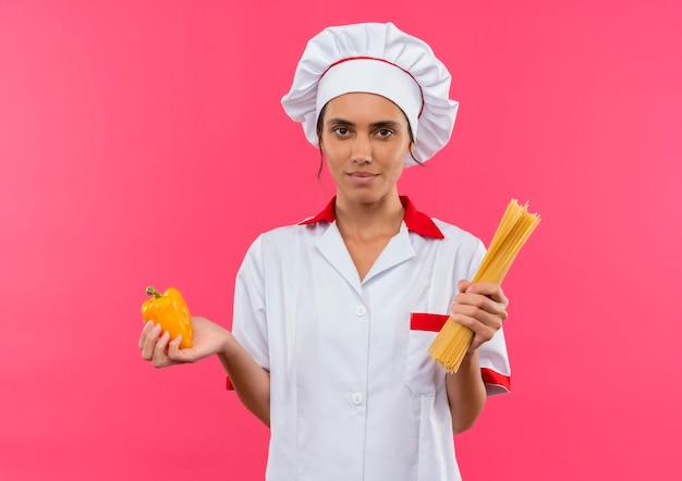 Giovane cuoco femminile che indossa l'uniforme del cuoco unico che tiene gli spaghetti e il papper sulla parete rosa isolata con lo spazio della copia