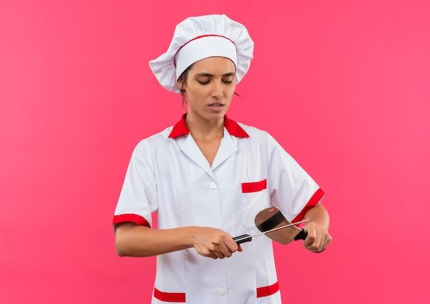 シェフの制服を着た若い女性料理人は、コピースペース付きの包丁でナイフを鋭くします