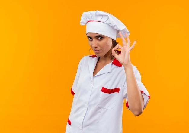 Молодая женщина-повар в униформе шеф-повара показывает жест в порядке на изолированной желтой стене с копией пространства