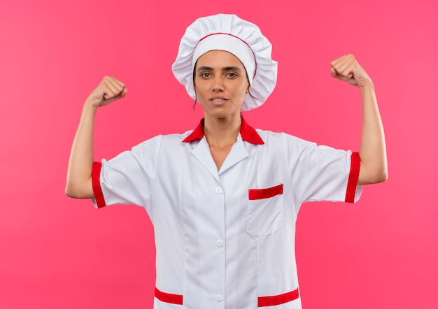 Young female cook wearing chef uniform showing strong gesture on isolated pink wall with copy space
