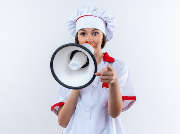 Young female cook wearing chef uniform speaks on loudspeaker isolated on white background