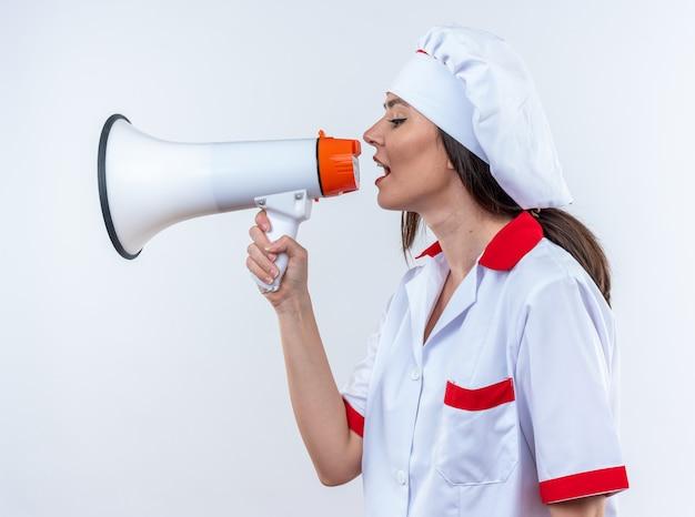 Молодая женщина-повар в униформе шеф-повара говорит по громкоговорителю, изолированному на белом фоне