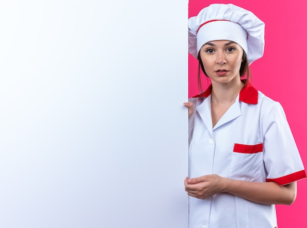 Young female cook wearing chef uniform stands nearby white wall isolated on pink wall with copy space