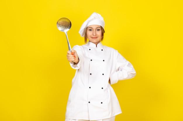 Молодая женщина готовит в белом поварском костюме и белой кепке позирует с серебряной ложкой