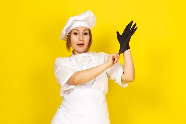 Молодая женщина готовит в белом поварском костюме и белой кепке в черной перчатке