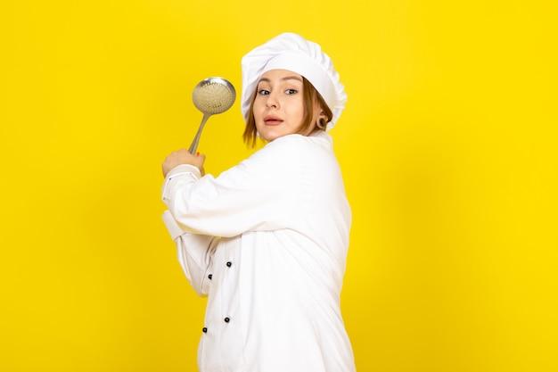 Giovane femmina di cucina in abito bianco cuoco e berretto bianco in posa pensando tenendo cucchiaio d'argento preparando a colpire