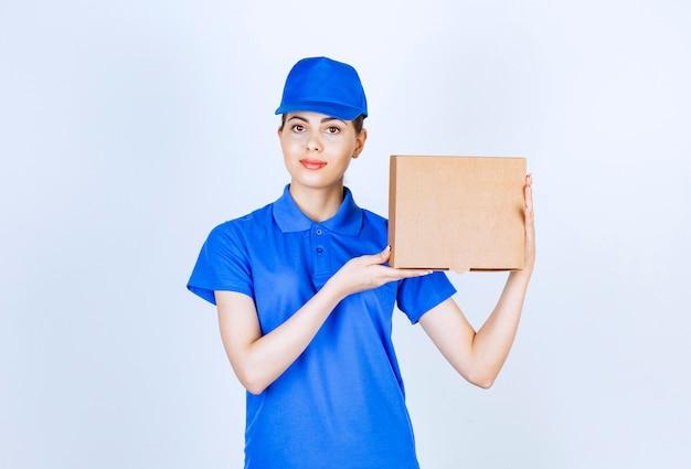 Giovane corriere femminile in uniforme blu che tiene scatola di cartone su sfondo bianco.