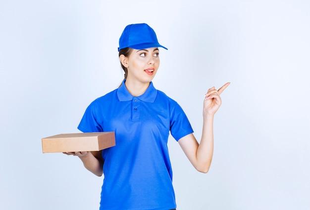 Giovane corriere femminile in uniforme blu in posa con scatola di cartone su sfondo bianco.