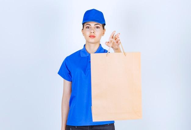 ペーパークラフトバッグを運び、白い背景の上に立っている若い女性の宅配便。