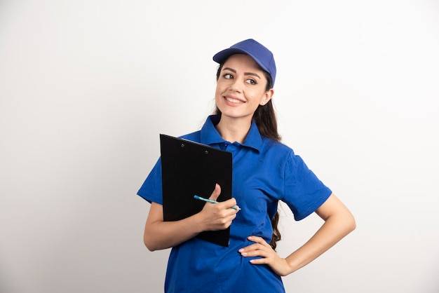 クリップボードを保持している青いスクラブの若い女性宅配便。高品質の写真