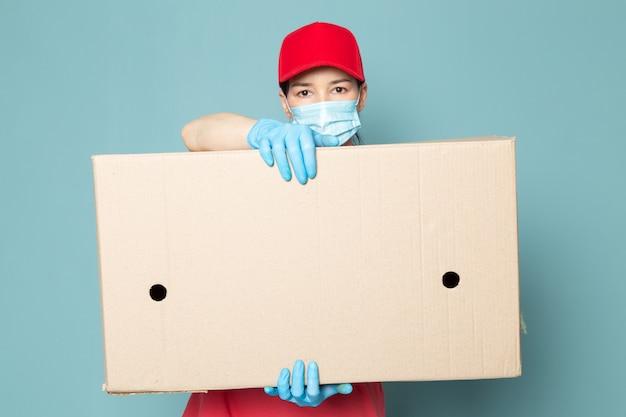 Молодая женщина-курьер в розовой футболке красной кепке держит коробку на синей стене