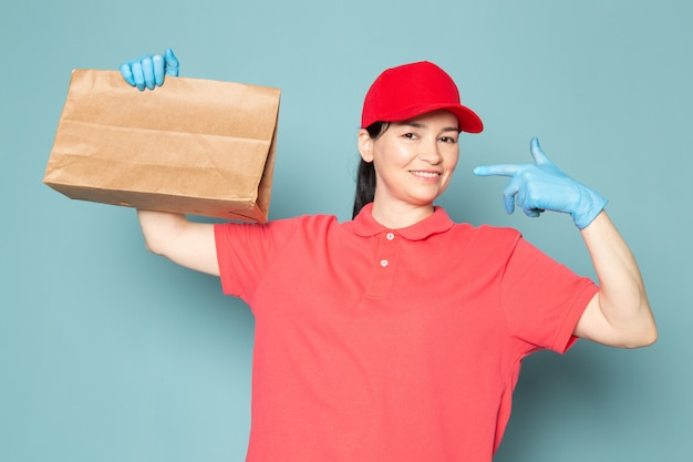 Young female courier in pink t-shirt red cap blue gloves holding box on the blue wall
