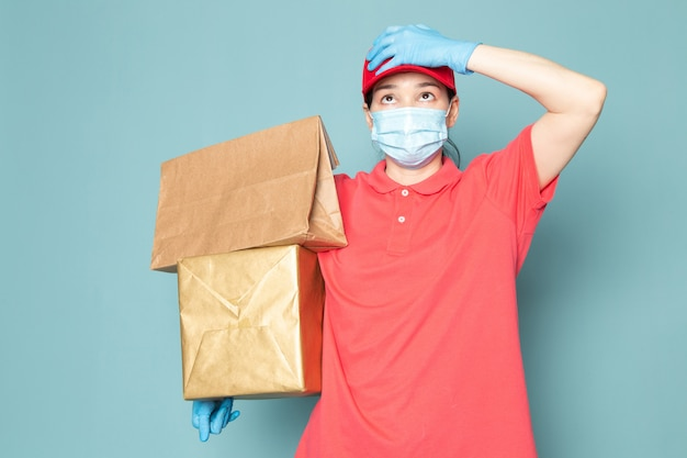 Young female courier in pink t-shirt red cap blue sterile mask blue gloves holding box on the blue wall