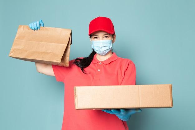 Giovane corriere femminile in maglietta rosa berretto rosso maschera blu sterile guanti blu tenendo la scatola sul muro blu
