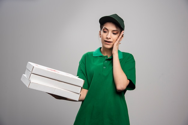 Young female courier posing with pizza boxes and covering her ear.