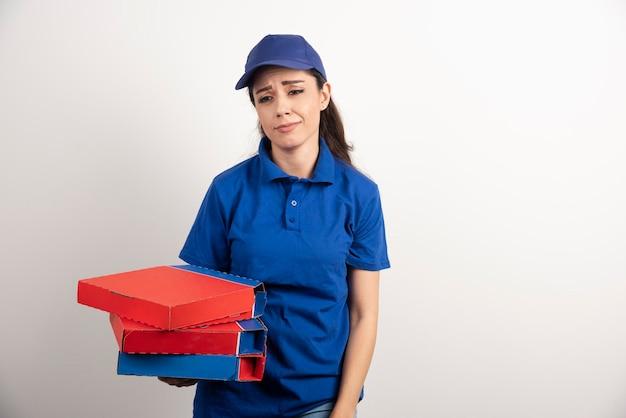 ピザとクリップボードの段ボールを持つ若い女性宅配便
