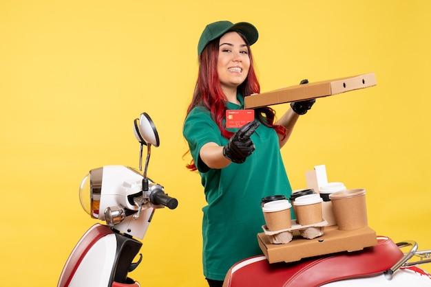Молодая женщина-курьер с доставкой кофе и еды на желтом