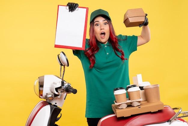 黄色の配達コーヒーと食品パッケージを持つ若い女性宅配便