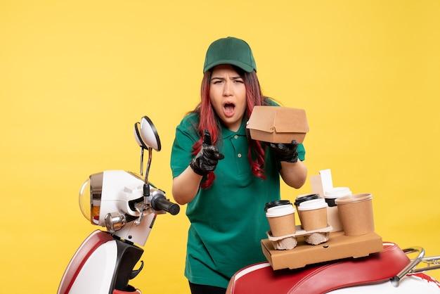 Giovane corriere femminile con consegna caffè e pacco alimentare su giallo on