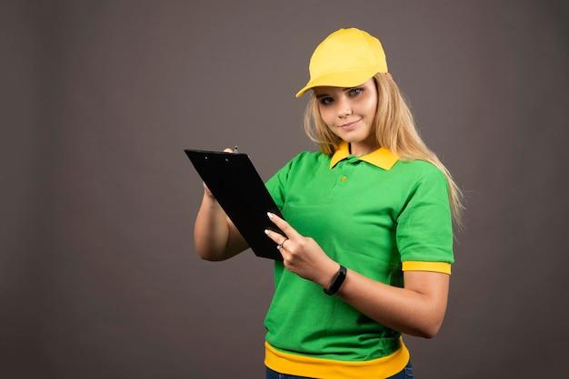 鉛筆とクリップボードを持つ若い女性の宅配便。高品質の写真