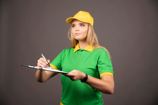 目をそらしている鉛筆とクリップボードを持つ若い女性の宅配便。高品質の写真