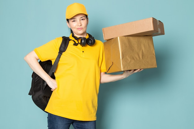 Young female courier in yellow t-shirt yellow cap holding box on the blue wall