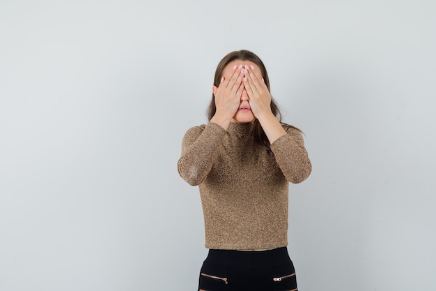 Young female covering eyes with hands in blouse,skirt and looking anxious , front view.