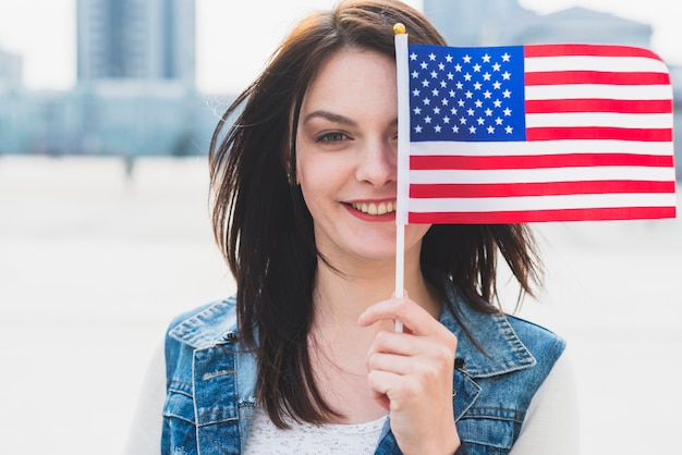 Young female covering face with american flag