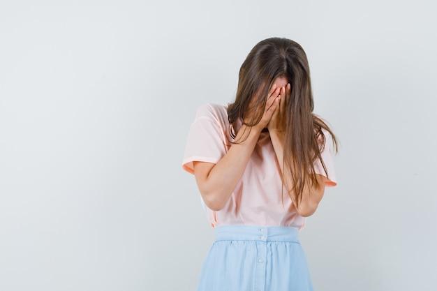 Tシャツ、スカートで手で顔を覆い、悲しそうに見える若い女性。正面図。