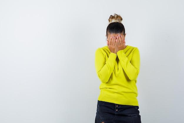 Giovane donna che copre il viso con le mani in maglione, gonna di jeans e sembra malinconica
