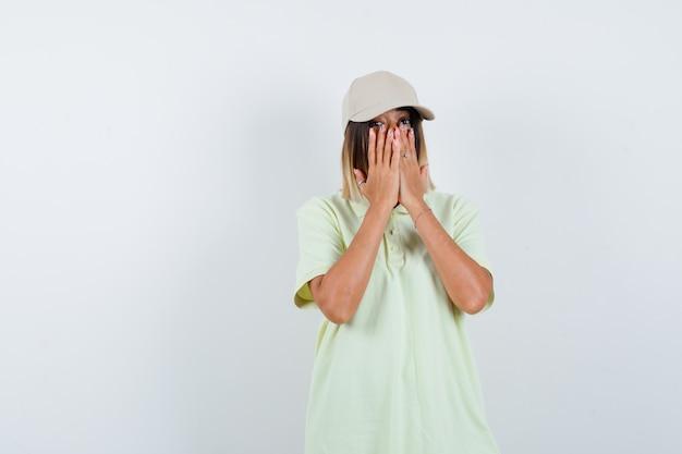 T- 셔츠, 모자에 카메라를보고 놀 랐 다, 전면보기 동안 손으로 얼굴을 덮고 젊은 여성.