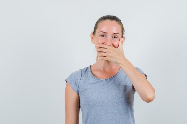 Молодая женщина, прикрывая рот, смеясь в серой футболке, вид спереди.