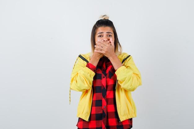 市松模様のシャツ、ジャケットで手で口を覆い、ショックを受けた若い女性。正面図。